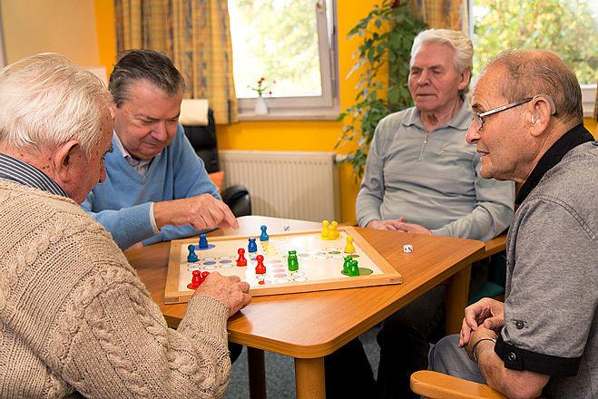 Bewohner einer Tagespflege mit einem Brettspiel